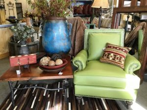 Image of furnishings showroom with green armchair and blue vase on wood and iron table